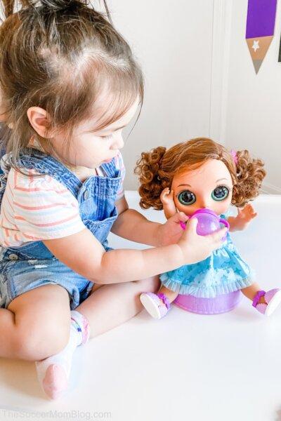 little girl giving baby doll a bottle