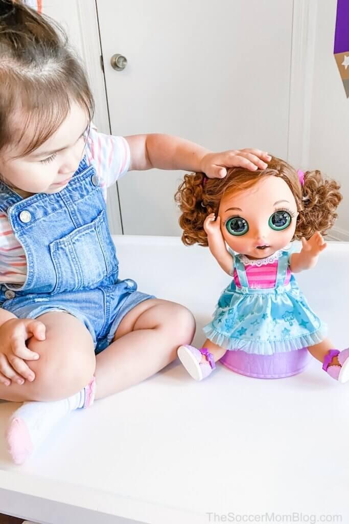 little girl patting baby doll