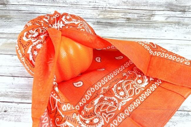 wrapping a craft pumpkin in an orange bandana