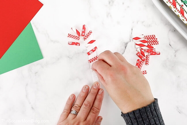 gluing red paper straws on paper to make a candy cane ornament