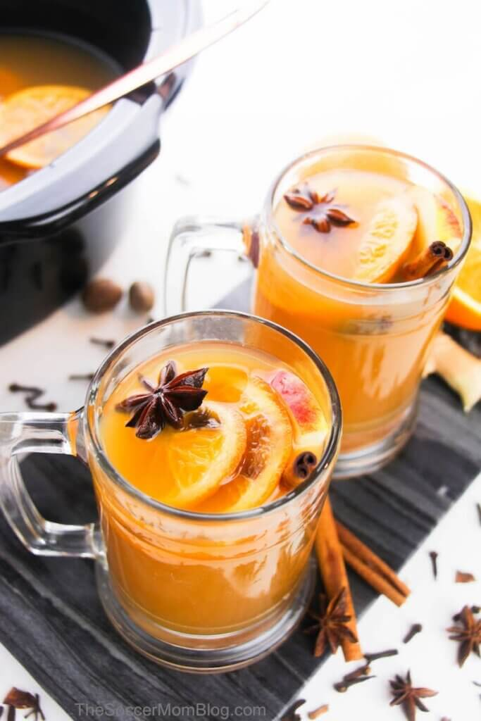 two mugs of spiced apple cider wth oranges and star anise