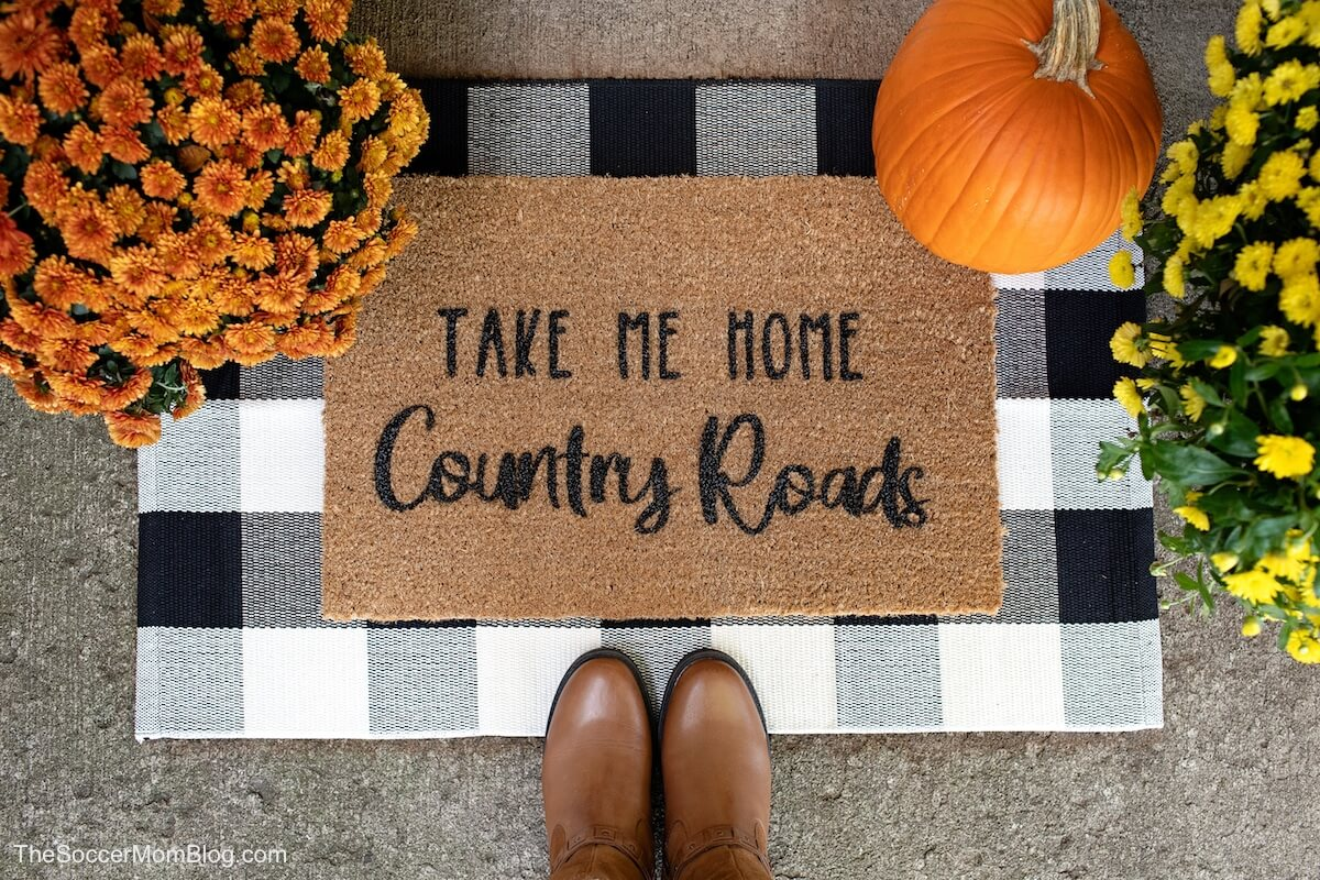 DIY Cricut door mat on concrete porch surrounded by boots and flowers