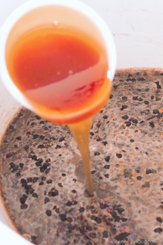 pouring honey into homemade elderberry syrup