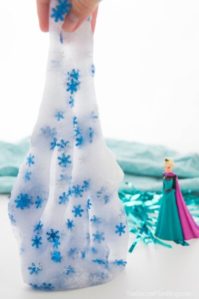stretching frozen slime with snowflake glitter next to Elsa doll