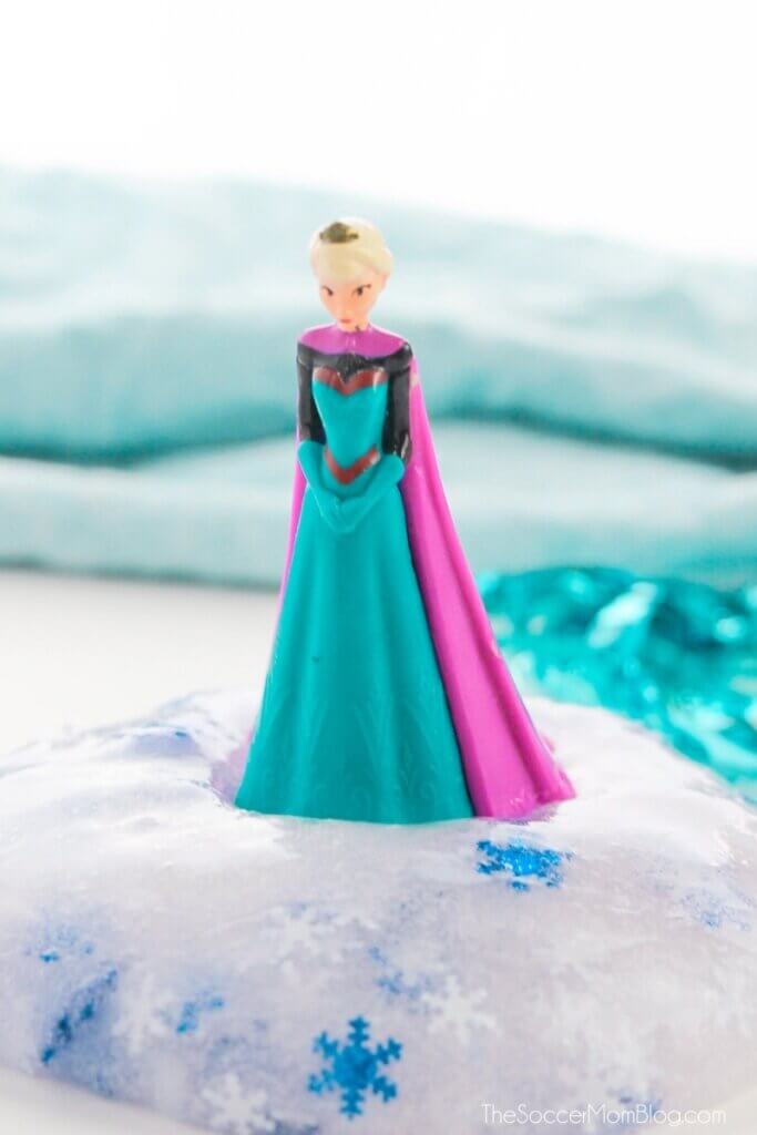 Elsa figurine standing on top of a ball of snowflake slime