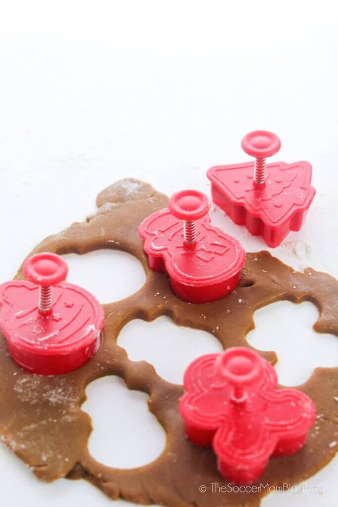 cutting Christmas cookie shapes out of gingerbread dough