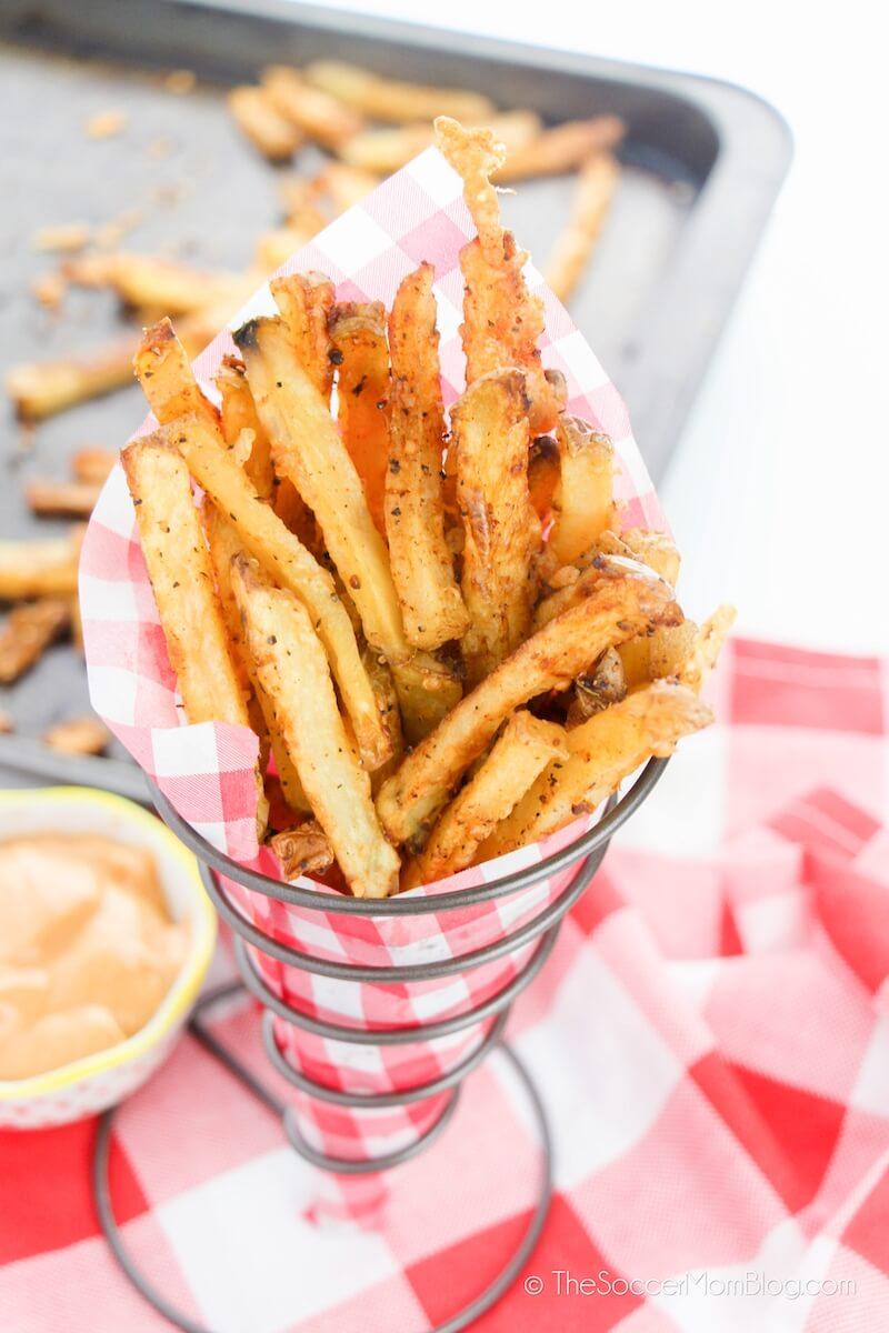 seasoning French Fries in standing basket
