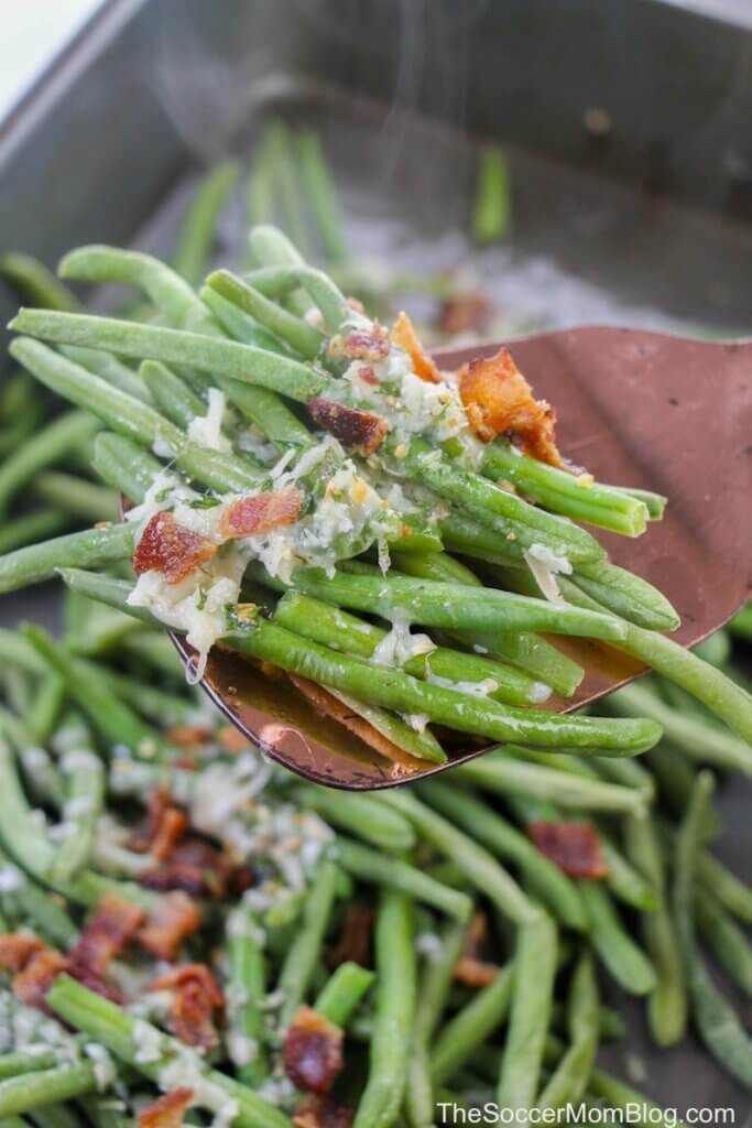 crisp roasted green beans on spatula with parmesan and bacon