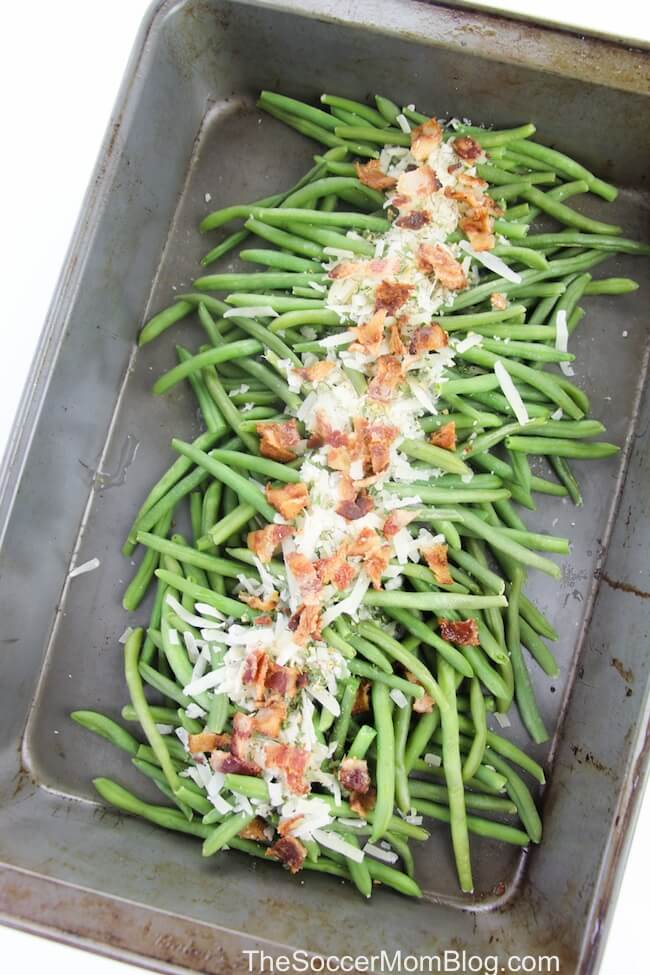 green beans in baking pan with cheese and bacon