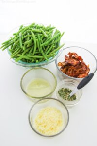 green beans in bowl, cheese in bowl, bacon in bowl