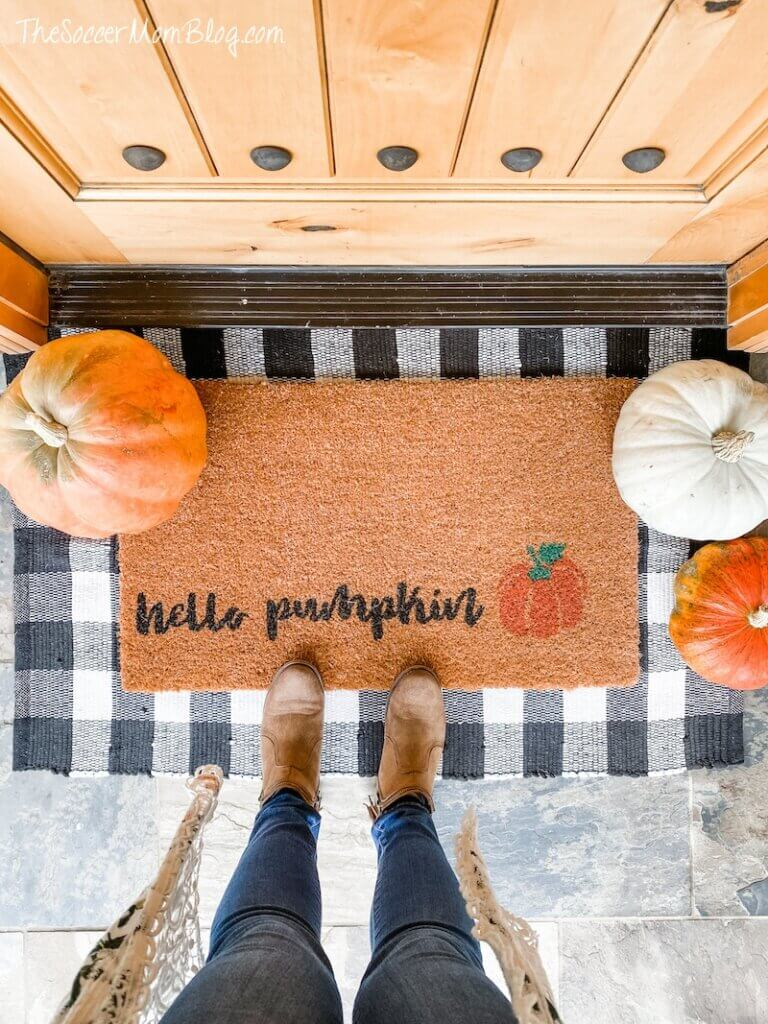 pumpkins and fall themed doormat on porch
