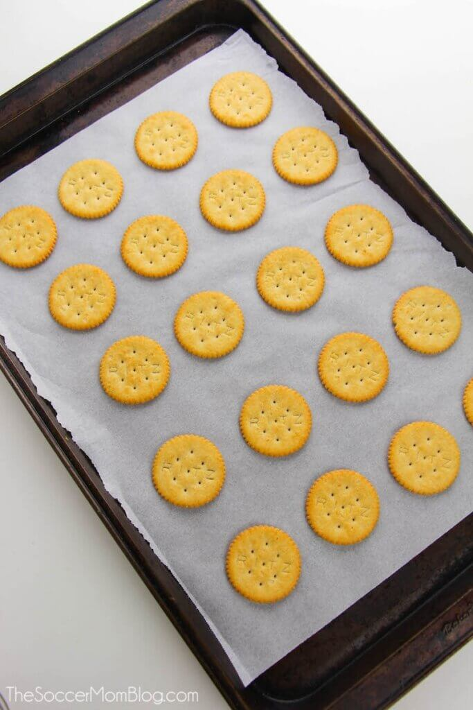 Ritz crackers on a parchment paper lined cookie sheet