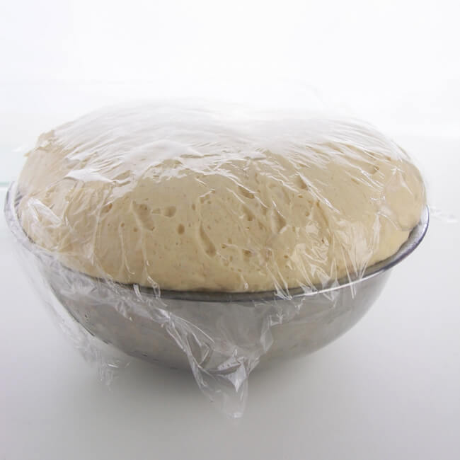 puffy bread dough rising in bowl on counter, covered in plastic wrap