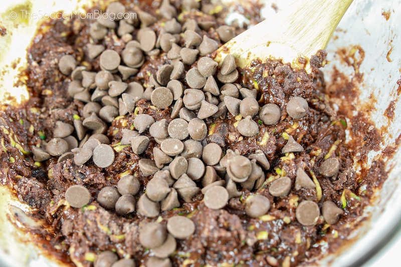 stirring chocolate chips into zucchini brownie batter
