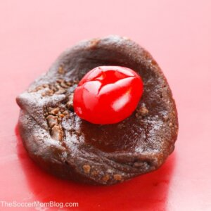 putting cherry in the middle of a chocolate cookie