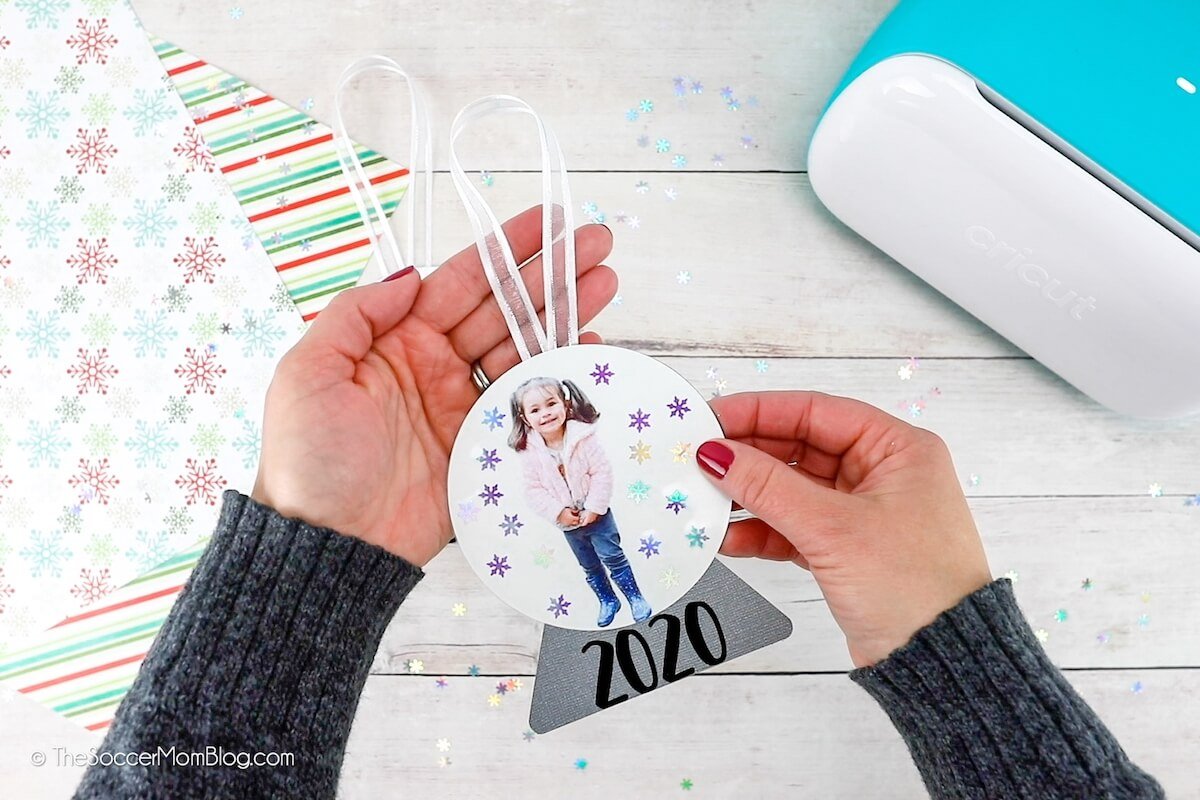 holding a paper snow globe ornament with child's photo