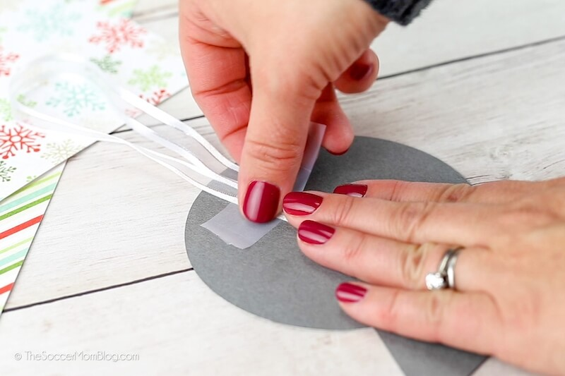 taping ribbon to the back of a paper snow globe ornament