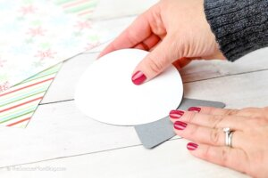 gluing white cardstock to make a paper snow globe ornament