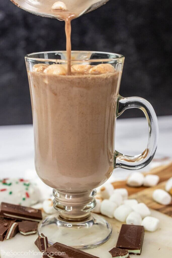 pouring hot cocoa into glass mug