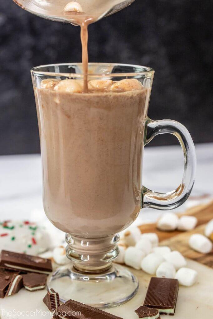 Gießen von heißem Kakao in Glasbecher