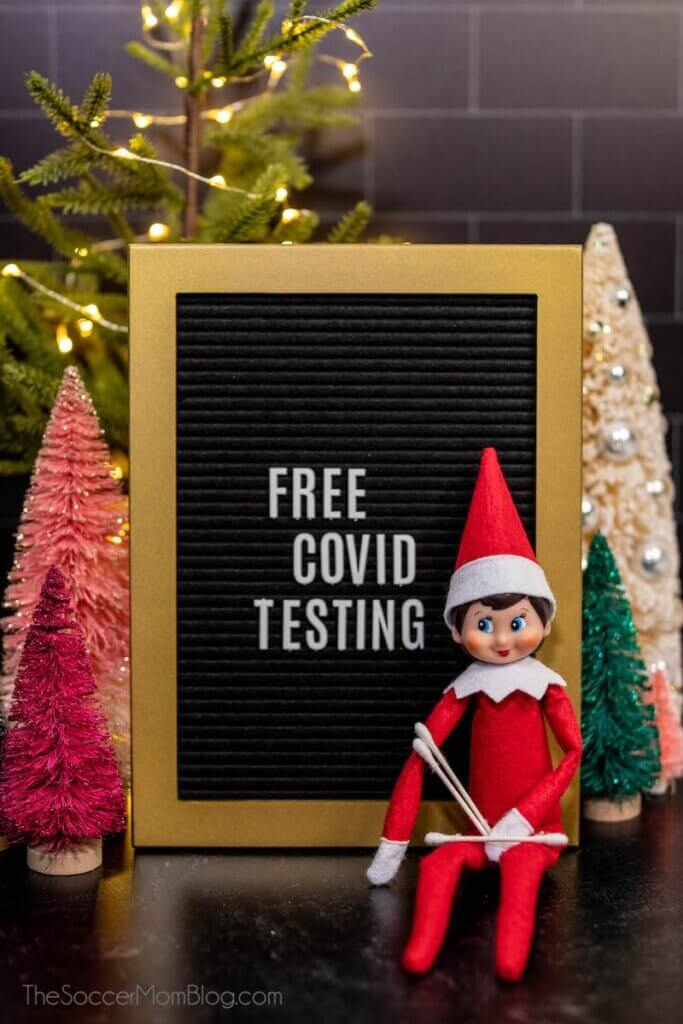 "Elf on the Shelf with q-tips and sign saying ""free COVID testing"""