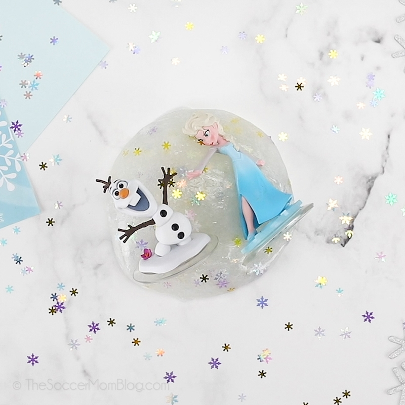 Elsa and Olaf figurines laying in a puddle of clear slime with snowflake glitter