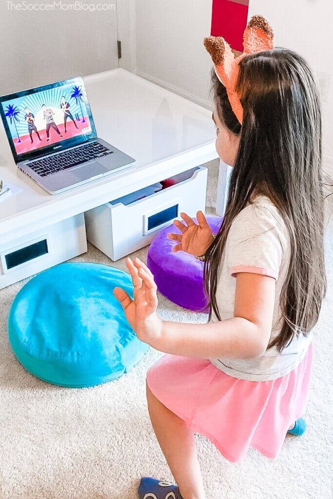 little girl dancing with music video on computer