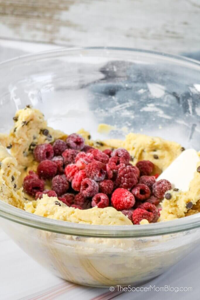 mixing raspberries into chocolate chip cookie dough batter