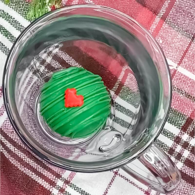Grinch hot chocolate bomb in the bottom of a glass mug
