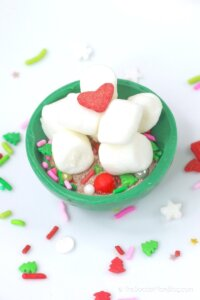 filling a green cocoa bomb with cocoa mix, marshmallows, and sprinkles