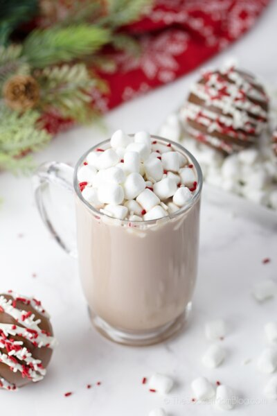 mug full of hot cocoa and marshmallows surrounded by hot cocoa bombs