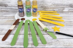painting craft sticks green and yellow