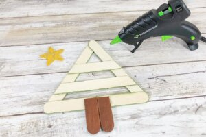 gluing together craft sticks to make a Christmas tree