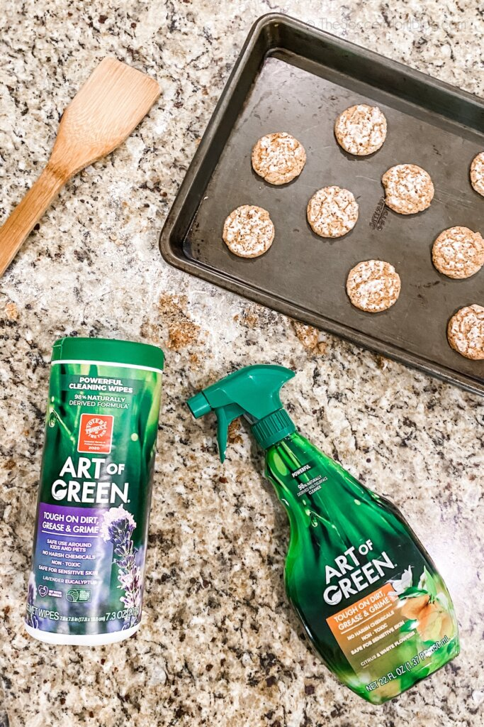 Art of Green cleaning products on countertop with tray of cookies