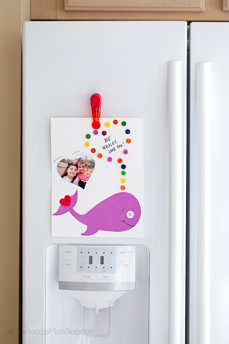 kid-made whale Valentine's Day card hanging on fridge