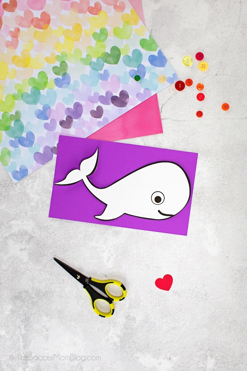 cutting a whale shape out of purple cardstock using a printable pattern