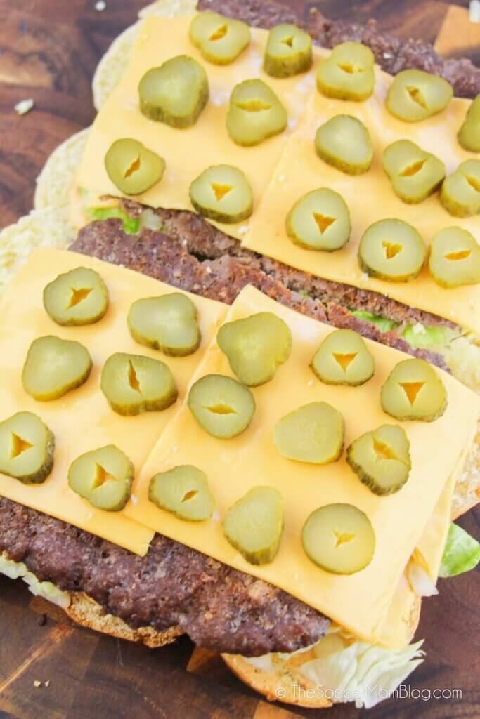 layering cheese and pickles on top of hamburger sliders