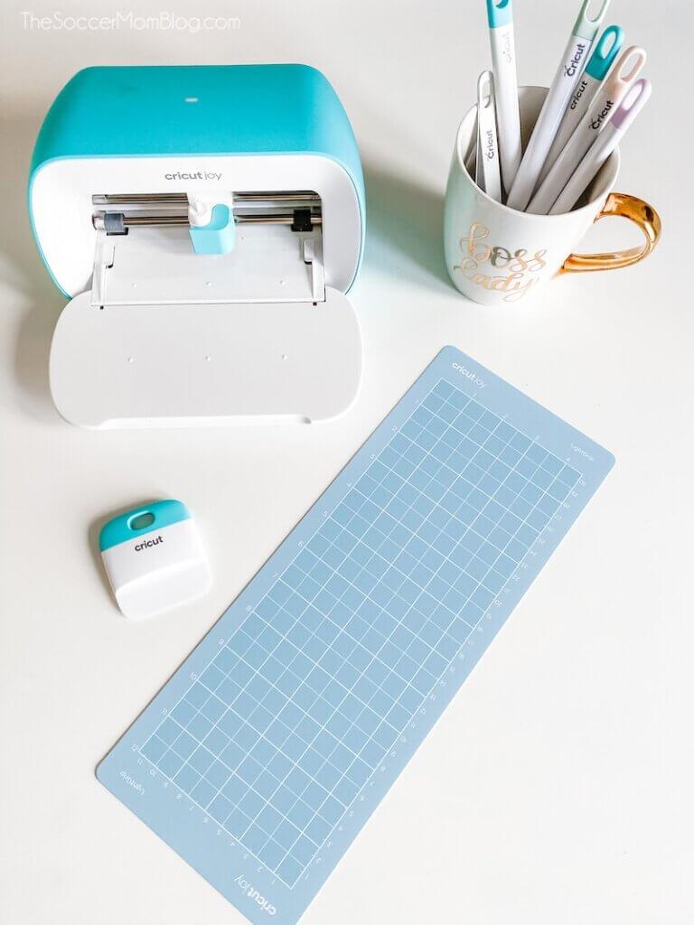 Cricut Joy machine and tools on white workspace