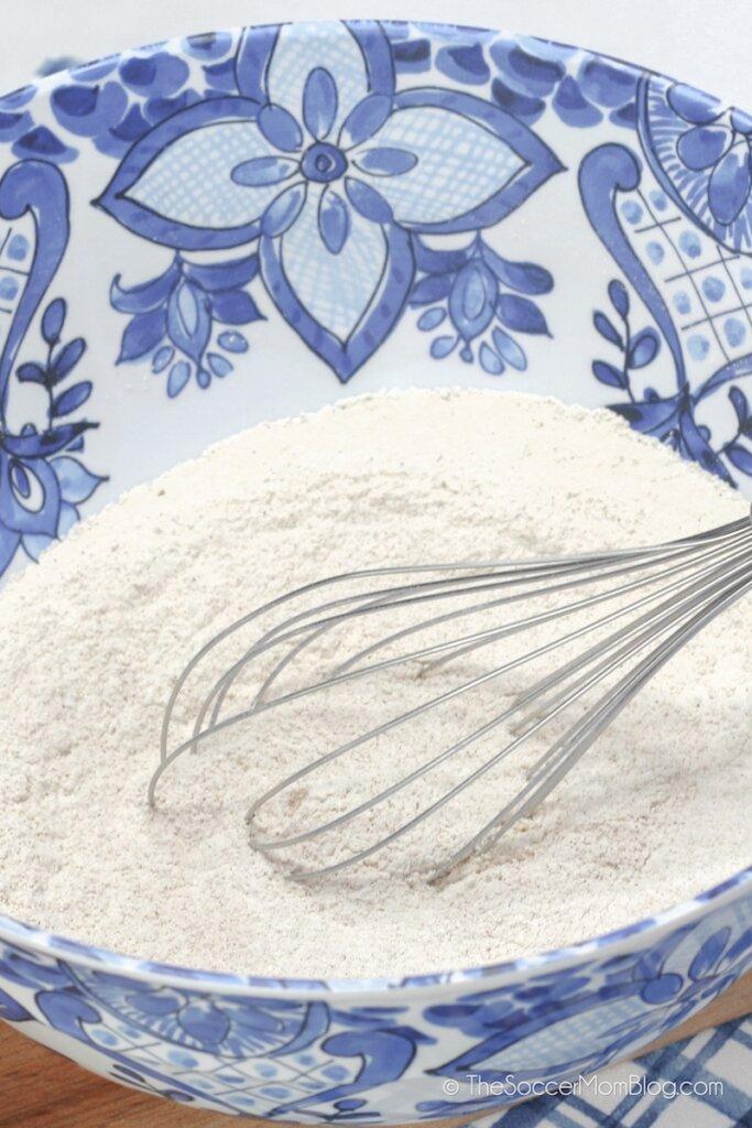 whisking dry cake ingredients in mixing bowl
