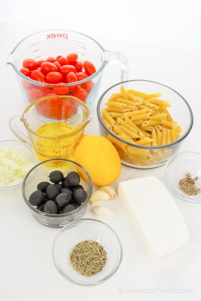 measuring cups with tomatoes, pasta, olives, and spices