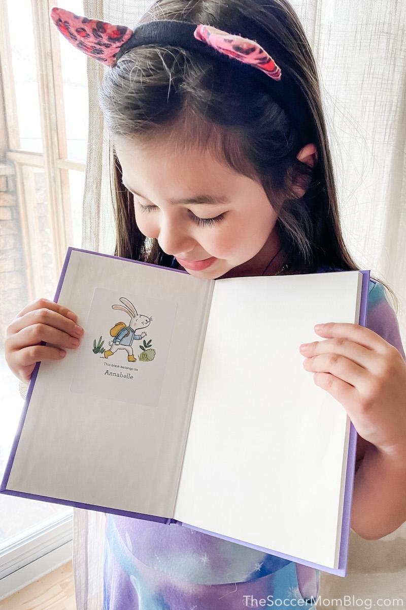 little girl holding open book