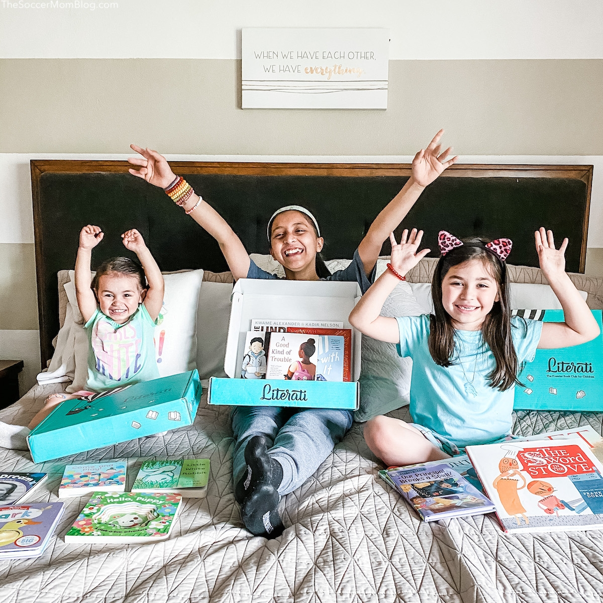 kids holding Literati book club boxes and cheering