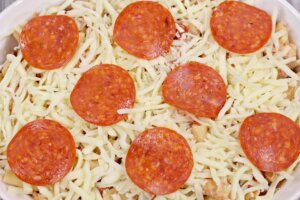 pasta casserole topped with shredded cheese and pepperoni