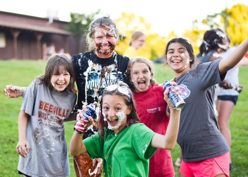 girls at summer camp playing with shaving cream