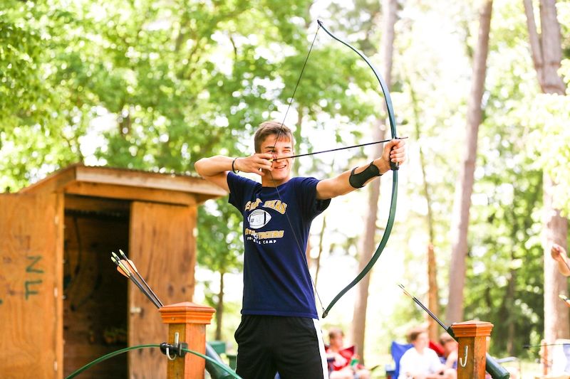 boy practicing archery at summer camp