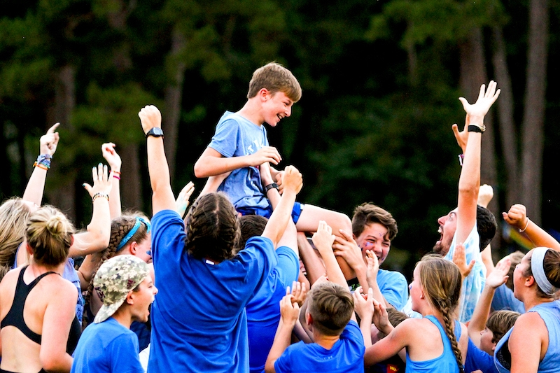 kids at summer camp lifting up another kid on their shoulders