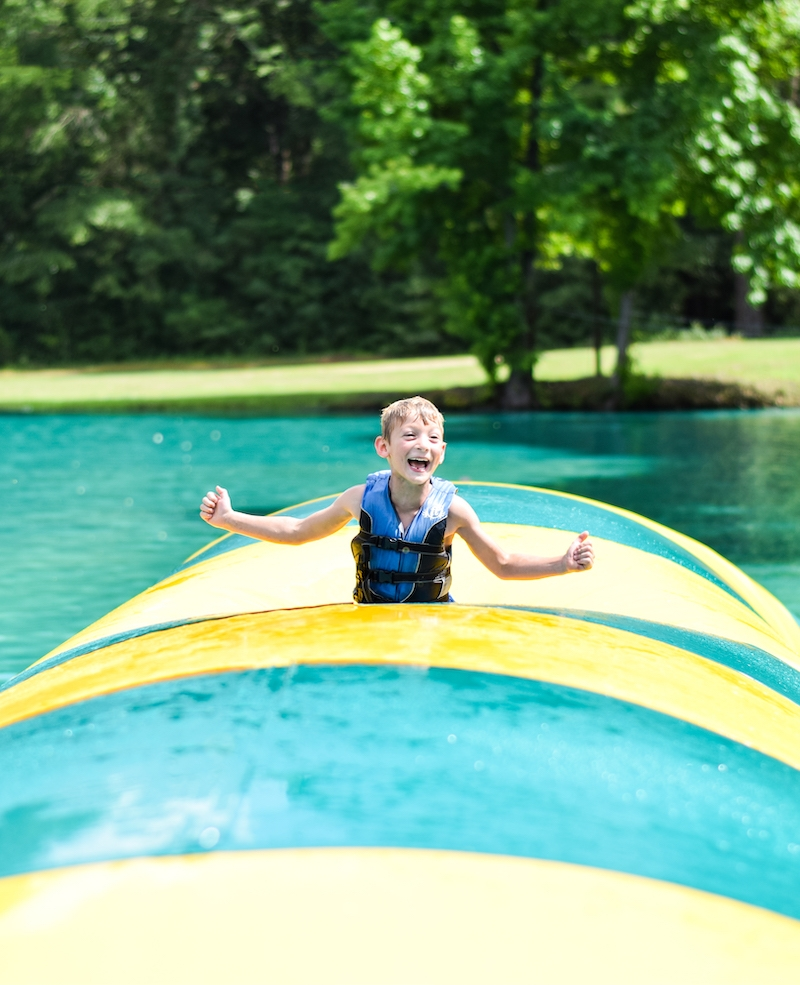 little boy on inflatable float in lake
