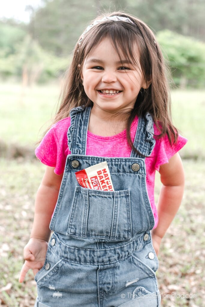 little girl wearing overalls and laughing