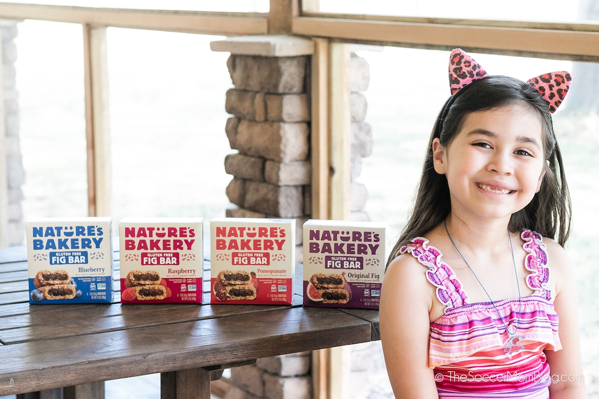 little girl sitting at picnic table with Nature's Bakery snacks