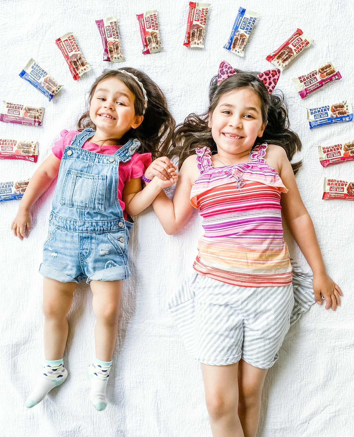 little girls lying down on picnic blanket with snack bars